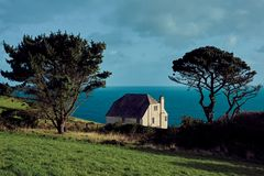 A white house on the coastline of Cornwall stock images