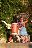 Young girl with Longhorn statue. Texas little girl, confident with a Texas Longhorn Royalty Free Stock Photography