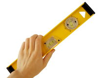 Spirit level. Yellow spirit level at human hand on white Royalty Free Stock Images