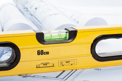 Spirit level and architecture blueprints. Blue tone Stock Photography