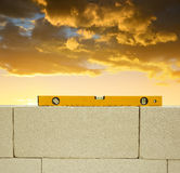 Spirit level on brick wall at sunset. Royalty Free Stock Images