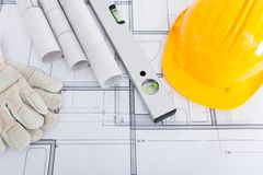 Spirit level; hardhat and gloves on blueprint Royalty Free Stock Images