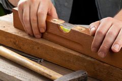 Spirit level. Old used water-level on wooden plank - do-it-yourself or artisan concept Stock Image