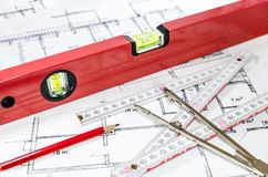 Spirit level and other measurement equipment lying on generic building plan. /blueprint stock image