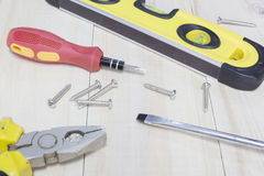 Spirit level , screwdriver , nut , plier on wooden Stock Photo