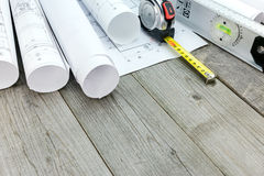 Spirit level with tape measure and rolls of architectural bluepr Royalty Free Stock Image