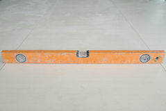 Spirit level tool on floor tile Royalty Free Stock Images