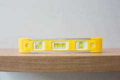 Spirit level on wooden surface against the wall Stock Photos