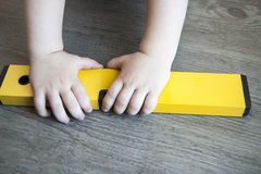 Spirit level in young boy hand - child with waterlevel Stock Photos