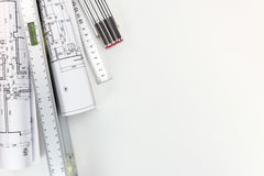 Spirit level and zigzag ruler with rolls of architectural bluepr Royalty Free Stock Photo