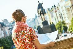 Traveller woman on Wenceslas Square in Prague with map. The spirit of old Europe in Prague. Seen from behind modern traveller woman on Wenceslas Square in Prague royalty free stock image