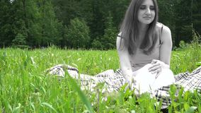 The spirit of a young woman sitting on the green grass in the park stock footage