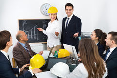 Spirited professionals with laptops and helmets having working m. Successful energetic spirited professionals with laptops and helmets having working meeting Royalty Free Stock Photo