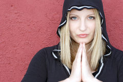 Spiritual adolescent woman. Adolescent,woman with hands clasped together. Her face framed with a black hooded shirt, Connection, spirituality Stock Images