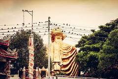 Spiritual Bangkok sights. Rear view of Sitting Buddha with birds on wires on foreground Stock Photos