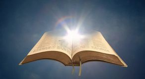 Spiritual bible light open holy book. Concept photo of open holy bible with sunlight shining through pages depicting divine spiritual light for mankind stock photography