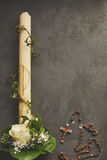 Spiritual border for Easter or a communion. With a white Eucharist candle entwined with a green vine, a posy of flowers in the corner and Catholic rosary on Stock Photos