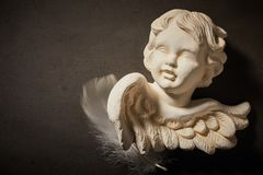 Memorial concept of angel figurine with feather. Spiritual concept of angel figurine with feather against dark background Stock Photo