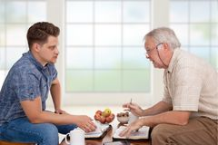 Spiritual counseling studying the Bible. Church servant doing spiritual counseling to a young men studying the Bible Royalty Free Stock Image