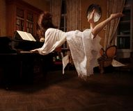 Spiritual dream about the music. Flying Girl playng piano - Spiritual dream about the music royalty free stock images