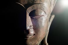 Spiritual enlightenment. Buddha head with divine light. Bronze s. Tatue face in close up against black background with copy space Royalty Free Stock Images