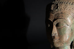 Spiritual enlightenment. Buddha statue head with copy space. Zen buddhism in the spotlight Stock Image