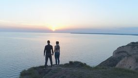 Spiritual freedom, sports happy couple enjoying calmness in nature near sea in sunset standing on hill shore. Drone view stock video