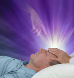 Spiritual help during a healing session. Female hands laid on a male patient`s forehead channeling energy together with a higher power manifesting healing light royalty free stock image
