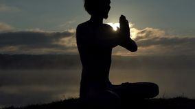 Spiritual man sits on a lake bank and practices yoga at sunset in slow motion. Slow motion - An inspiring view of a young man who sits in a lotus asana on a lake stock footage