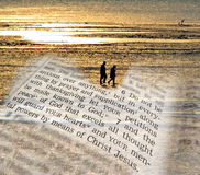 Spiritual peace of mind. Composition photo of a couple walking on the beach at low tide with the setting sun reflecting on the water and a superimposed bible Stock Photography