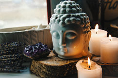 Spiritual ritual meditation face of Buddha ametist candles on old wooden background stock photos