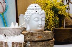 Spiritual ritual meditation face of Buddha on wood, home decor, mimosa yellow spring flowers. still life Royalty Free Stock Photography