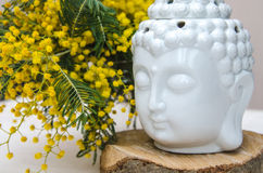 Spiritual ritual meditation face of Buddha on wood, home decor, mimosa yellow spring flowers Stock Photo