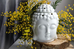 Spiritual ritual meditation face of Buddha on wood, home decor, mimosa yellow spring flowers Stock Photos