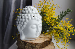 Spiritual ritual meditation face of Buddha on wood, home decor, mimosa yellow spring flowers Royalty Free Stock Photography