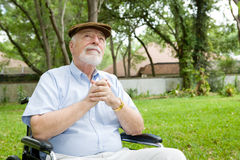 Spiritual Senior Man. Senior man in wheelchair praying, in a beautiful outdoor setting Royalty Free Stock Photo