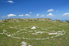 The spiritual symbol of The White Brotherhood. Drawn by white stones on the green grass circle with pentagram in it - the spiritual symbol of The White Stock Images