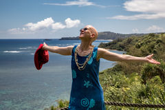 Spiritual, thankful woman, Anini Bay, Kauai. A smiling, thankful, spiritual woman with arms open wide looking skyward to the heavens in a tropical setting Royalty Free Stock Images