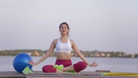 Spiritual world, young lovely yogi woman in lotus position meditates and delight spiritual calmnes on open air. Near water stock video footage