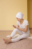 Spiritual young woman with a phone after yoga Stock Images