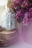 Spiritual zen meditation face of Buddha with beautiful violet branch lilac flowers. Home decor, still life concept Royalty Free Stock Image