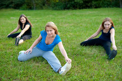 Spirituality exercising in nature of cute girls. Meditation in nature - Cute young girls relaxing outdoor on a green grass field in park Royalty Free Stock Image