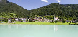Spirituality in the Mountains. A small church along the turquoise blue waters of Auronzo Lake in northern Italy Royalty Free Stock Photography