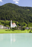 Spirituality in the Mountains. A small church along the turquoise blue waters of Auronzo Lake in northern Italy Stock Photo