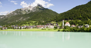 Church in the Mountains. A small church along the turquoise blue waters of Auronzo Lake in northern Italy with the Three Chimneys in the background Stock Image