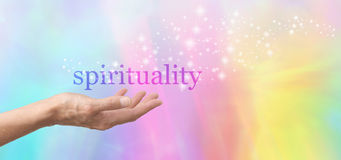 Spirituality in the Palm of your Hand. Female hand outstretched and facing upwards with the word 'spirituality' floating above on a rainbow colored background Royalty Free Stock Image