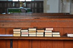 Spiritually Uplifting Hymn books stacked on church bench. A stack of hymn books containing many spiritually uplifting songs sit on an old discolored wooden royalty free stock images