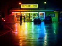 Spirituosenladen auf einer nassen regnerischen Nacht Lizenzfreie Stockfotos