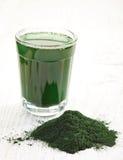 Spirulina algae powder. Stack of spirulina algae powder and spirulina drink white wooden background Stock Image