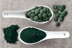 Spirulina algae powder and tablets. On gray background from top view Stock Image